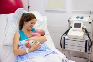 Mãe abraçando bebê recém-nascido.