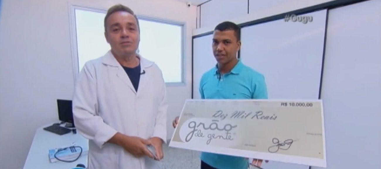 Dieyzo, pai de Emanuelly, recebe o cheque com a doação da Grão de Gente