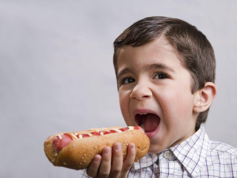 Menino comendo hot dog. Os riscos de crianças comerem embutidos.